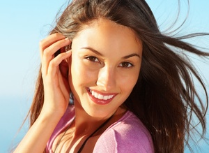 Closeup of pretty young woman smiling with windswept hair